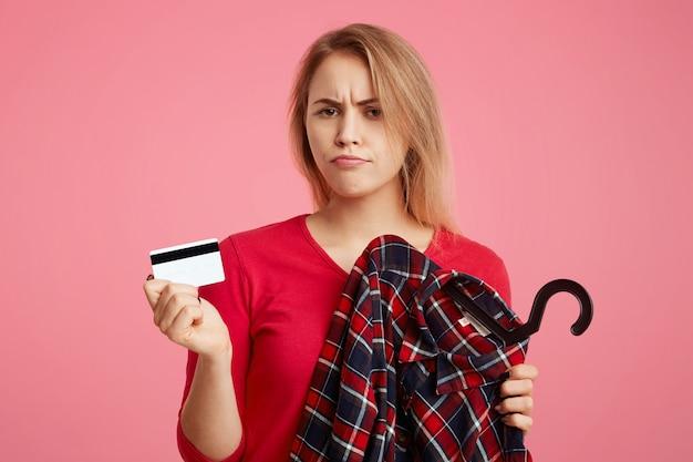 Foto de mulher adorável com expressão de descontentamento vai às compras na boutique elegante, escolhe roupa, segura o cartão de plástico