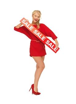 Foto de mulher adorável em vestido vermelho com placa de venda