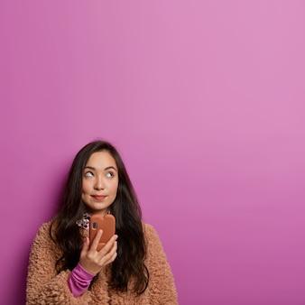 Foto de mulher adorável pensativa fica com celular moderno, olha em algum lugar, tem ideia interessante, recebe proposta curiosa, vestida com casaco marrom