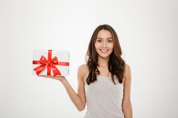 Foto de mulher adorável, segurando a caixa embrulhada para presente com laço vermelho, sendo animado e surpreso ao receber o presente de férias, isolado sobre o branco