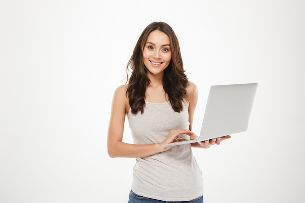 Foto de mulher afável com cabelos castanhos compridos, segurando o computador pessoal prateado posando na câmera, isolada sobre a parede branca