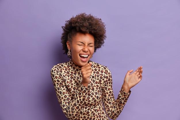 Foto de mulher afro-americana alegre segura a mão perto da boca como microfone, canta canções no karaokê, feliz e usa roupas com estampa de leopardo