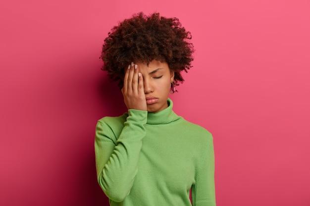 Foto de mulher afro-americana cansada cobre metade do rosto com a palma da mão, mantém os olhos fechados, quer dormir, precisa descansar
