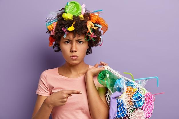 Foto de mulher afro-americana descontente com raiva com uso abusivo de plástico, aponta para saco com lixo coletado, tem resíduos na cabeça, isolados na parede roxa. conceito de poluição não reciclável