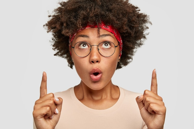 Foto de mulher afro surpresa com os dois dedos indicadores, mantendo a boca bem aberta