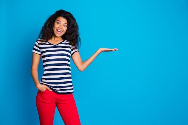 Foto de mulher alegre com a mão no bolso segurando algo, apresentação de produto, espaço de cópia na parede azul