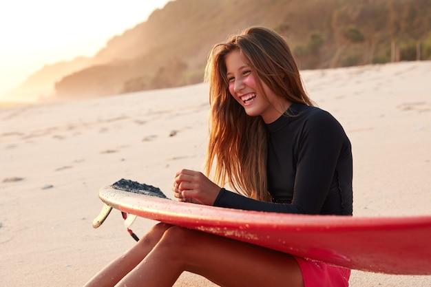 Foto de mulher alegre com cabelo comprido escuro, sorrindo feliz, se divertindo com a amiga surfista, vestida com roupa de neoprene