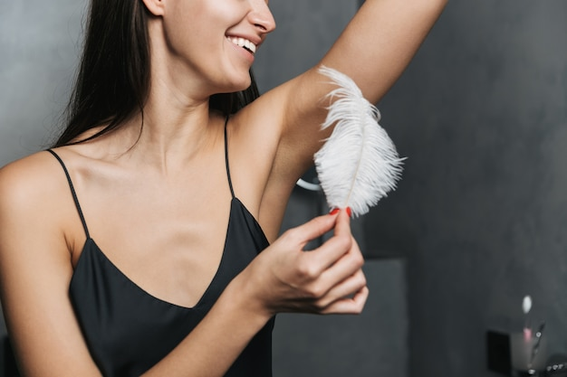 Foto de mulher alegre com longos cabelos escuros e pele limpa tocando seu corpo com uma grande pena