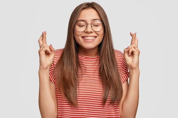 Foto de mulher alegre de cabelos escuros que acredita na boa sorte, mantém os dedos cruzados