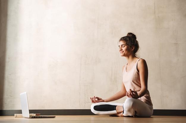 Foto de mulher alegre e fitness em roupas esportivas meditando com os dedos zen e sorrindo enquanto está sentada no chão com o laptop em casa