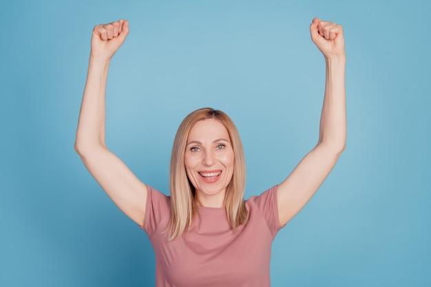 Foto de mulher animada, feliz sorriso positivo, alegria, vitória, sorte, sucesso, punhos, mãos isoladas, sobre, azul, cor, fundo