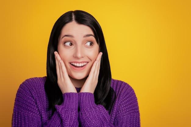 Foto de mulher animada olhando para o espaço vazio espantado surpreso toque mãos bochechas venda usar suéter isolado sobre um fundo de cor brilhante