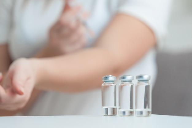 Foto de mulher aplicando injeção atrás de ampolas vazias