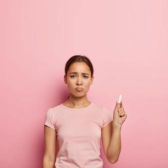 Foto de mulher asiática infeliz segurando tampão, tem expressão facial triste durante cãibras mensais, sofre de sensações dolorosas, usa camiseta casual, fica em um ambiente fechado. oh não, de novo menstruação.