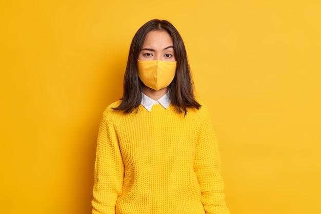Foto de mulher asiática jovem séria levanta sobrancelhas usa máscara protetora descartável e fica em casa durante a pandemia de coronavírus.