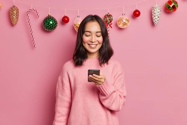 Foto de mulher asiática morena encantada com aparência oriental segura telefone celular moderno e envia mensagens de felicitações na véspera de ano novo usando poses casuais de macacão