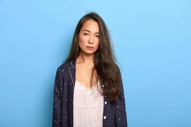 Foto de mulher asiática morena séria e insatisfeita olha com cansaço para a câmera, não dorme o suficiente, usa roupa de dormir