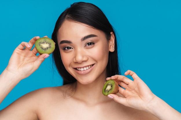 Foto de mulher asiática muito positiva posando isolada na parede azul com kiwi.