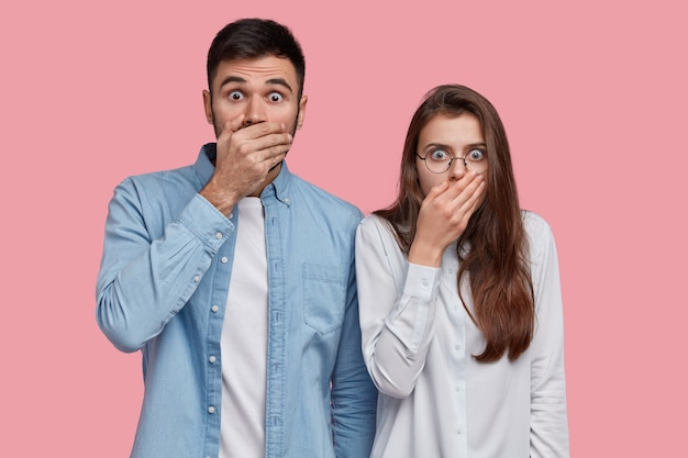 Foto de mulher assustada e muda com um homem cobrindo bocas com as palmas das mãos, com expressões estupefatas, vestido com uma camisa elegante