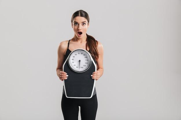Foto de mulher atlética morena segurando a balança e expressando surpresa no rosto, isolado sobre a parede cinza