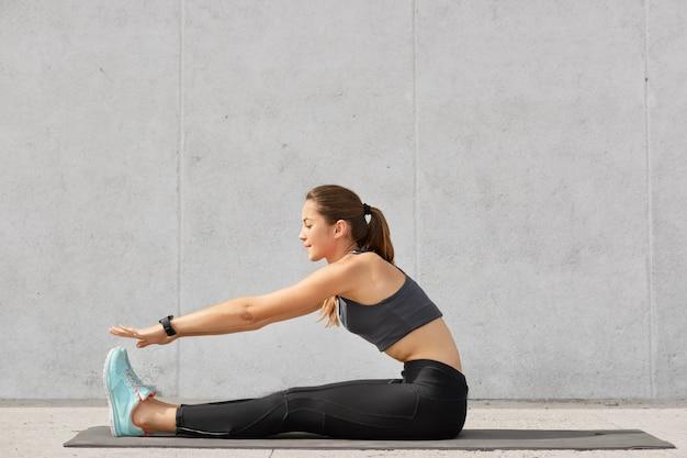 Foto de mulher atraente e desportiva com rabo de cavalo, figura perfeita, faz exercícios de alongamento na esteira, usa blusa casual, leggings e tênis