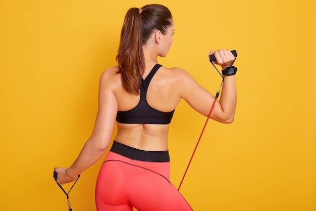 Foto de mulher atraente e desportiva realiza exercícios com banda de resistência