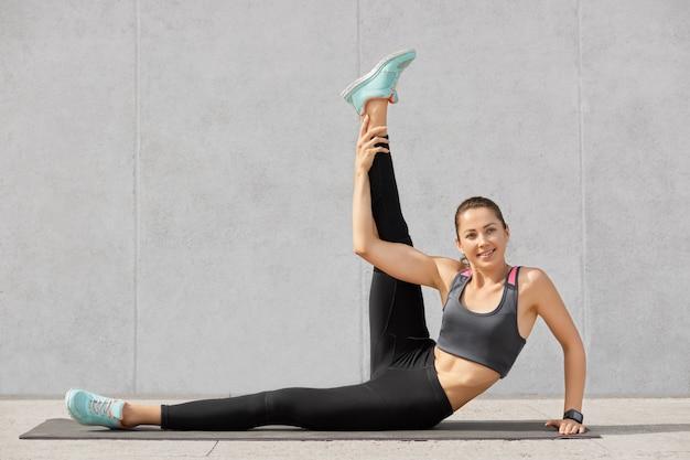 Foto de mulher atraente faz exercícios abdominais
