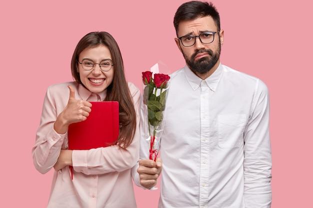 Foto de mulher atraente mostra gesto de aprovação, mantém o polegar levantado, carrega o bloco de notas vermelho, perplexo homem com a barba por fazer segurando buquê de rosas