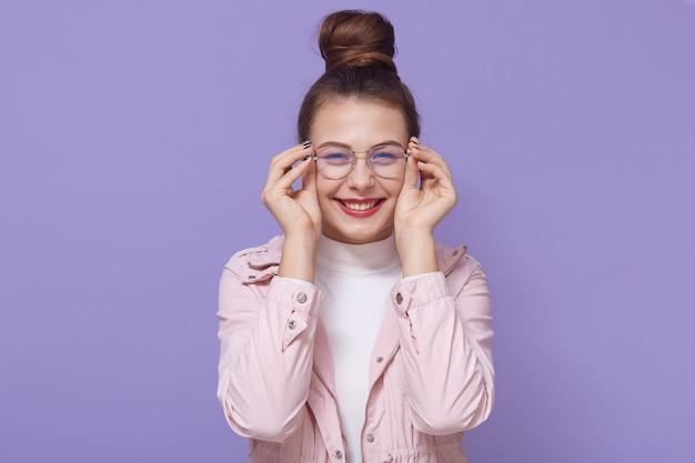Foto de mulher atraente parece curiosamente, tem uma expressão feliz, toca a moldura dos óculos, usa uma jaqueta rosa pálida, posando com um sorriso feliz isolado sobre o fundo lilás.