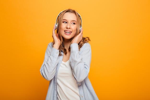 Foto de mulher bonita caucasiana usando aparelho tendo prazer enquanto desfruta de música favorita através de fones de ouvido modernos, isolados sobre o espaço amarelo