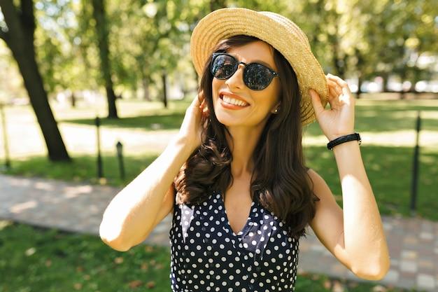 Foto de mulher bonita com cabelo curto escuro, vestida com um vestido bonito com um sorriso encantador. ela está usando chapéu de verão e óculos escuros pretos. belo retrato.