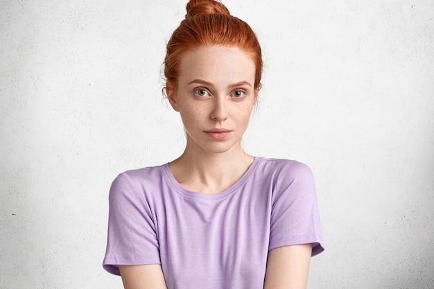 Foto de mulher bonita de cabelo ruivo sério, vestida com uma camiseta casual roxa, isolada sobre o estúdio branco