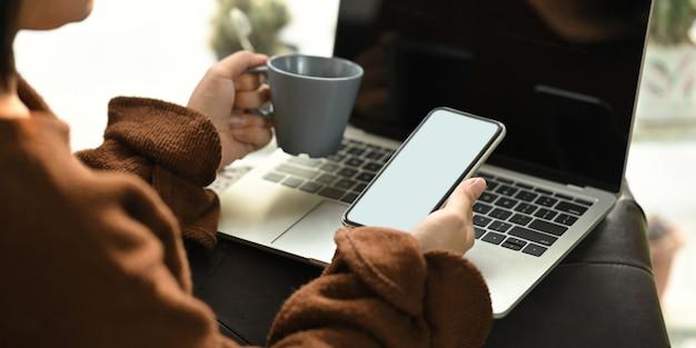 Foto de mulher bonita e relaxante em suas férias, sentado no sofá de couro e tomando um café quente enquanto estiver usando um laptop de computador de tela em branco branco que colocar no colo. mulher relaxar tempo.