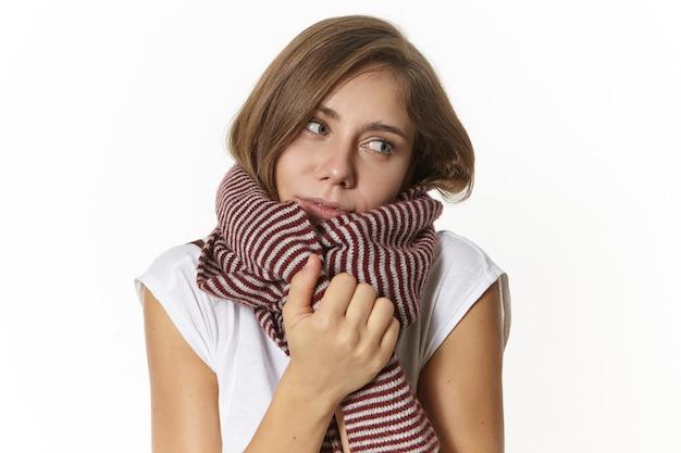 Foto de mulher bonita em uma camiseta branca se aquecendo e sendo envolvida em um lenço listrado de lã