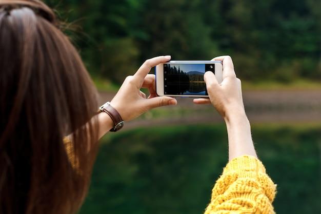 Foto de mulher bonita morena tirando foto de belas montanhas