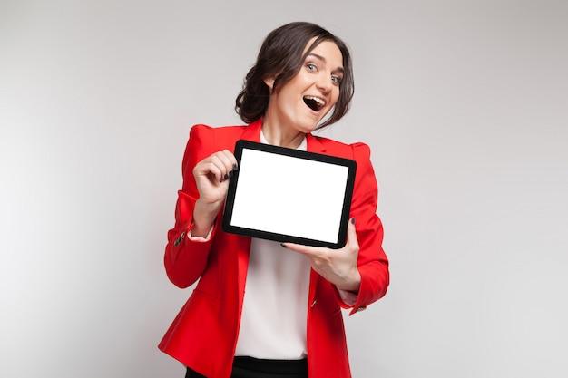 Foto de mulher bonita no blazer vermelho em pé com tablet nas mãos