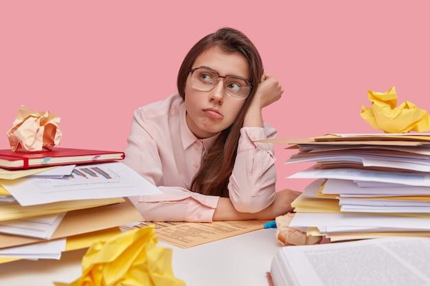 Foto de mulher cansada sem vontade de trabalhar, olha pensativamente para o lado, usa óculos grandes, tem muitos papéis para folhear, senta-se sozinha no trabalho