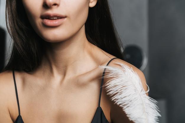 Foto de mulher caucasiana com longos cabelos escuros e pele limpa tocando seu corpo com uma grande pena