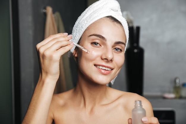 Foto de mulher caucasiana com uma toalha na cabeça, aplicando óleo cosmético no rosto