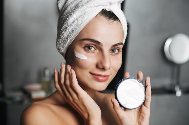 Foto de mulher caucasiana enrolada em uma toalha, aplicando creme no rosto