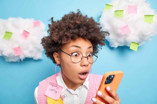 Foto de mulher chocada de cabelo encaracolado encara a tela do smartphone e descobre que foi reprovada no exame, tem muito trabalho a fazer, faz lembretes em adesivos prepara relatório isolado urgentemente na parede azul