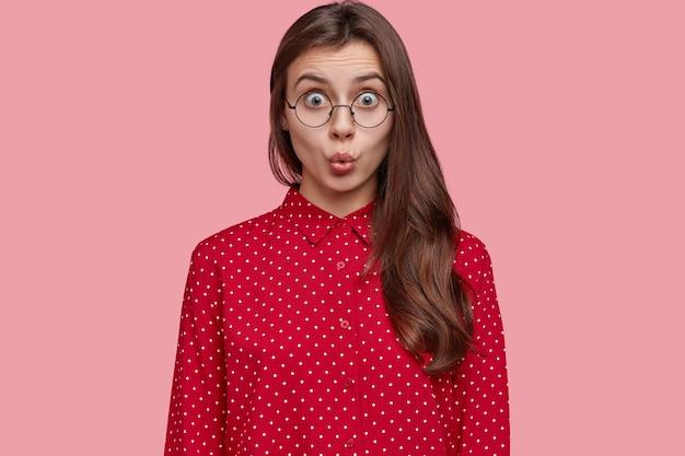 Foto de mulher chocada em estupor, com lábios redondos, em situação perturbadora, vestida com uma blusa de bolinhas da moda, usa óculos redondos