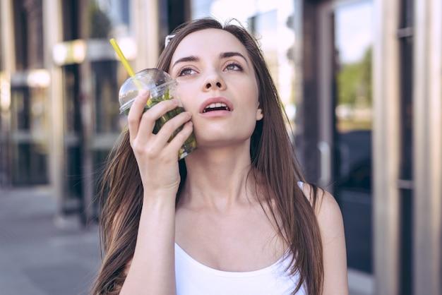 Foto de mulher colocando uma bebida gelada na bochecha