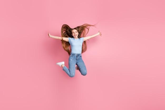 Foto de mulher com as mãos abertas pulando alto, isolada em um fundo de cor rosa pastel