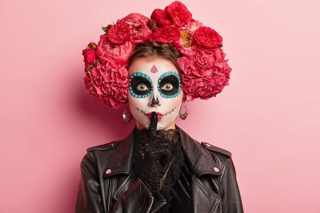 Foto de mulher com maquiagem tradicional e flores no cabelo, faz gestos silenciosos, mantém o dedo indicador sobre os lábios pintados, se prepara para a terrível festa da morte, vestida com roupa preta, isolada no rosa