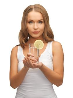 Foto de mulher com uma rodela de limão em um copo d'água