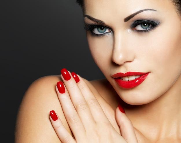 Foto de mulher com unhas vermelhas da moda e lábios sensuais