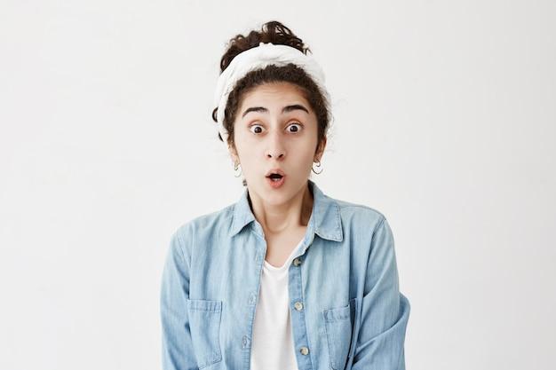 Foto de mulher de cabelos escuros surpreendida e chocada com pano branco mantém a boca aberta, olha com insatisfação ao descobrir seu grande fracasso na preparação para os exames. omg conceito