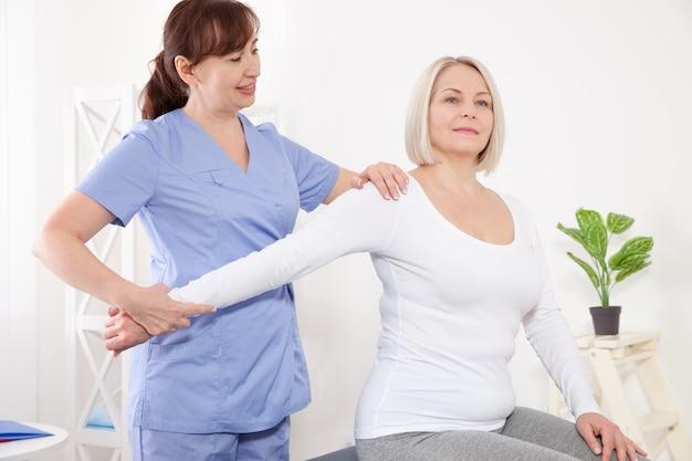 Foto de mulher de meia idade durante a reabilitação em clínica profissional