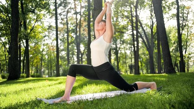 Foto de mulher de meia idade praticando ioga ou fitness na grama verde fresca no parque. saúde física e mental feminina. pessoa em meditação e harmonia de corpo e alma